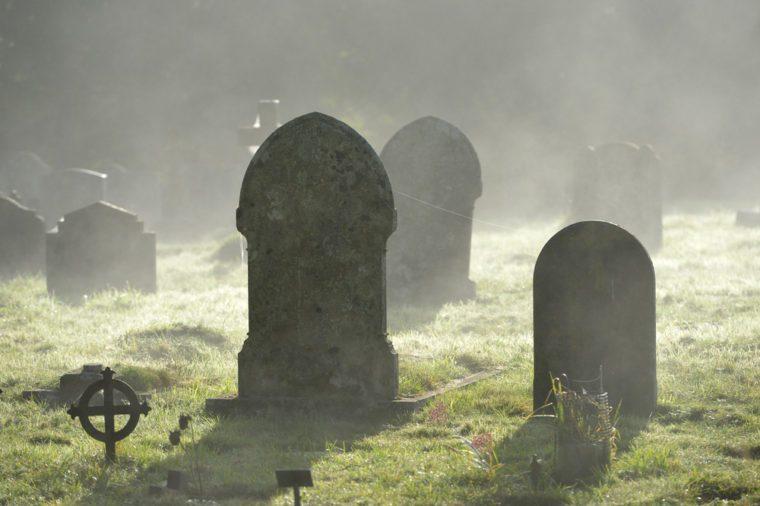Misty graveyard,crosses and graves backlit