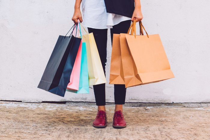 She is standing back from shopping. She wore black pants and a white coat.She Holds a variety of paper bags. Photo concept Shopping and relax time.