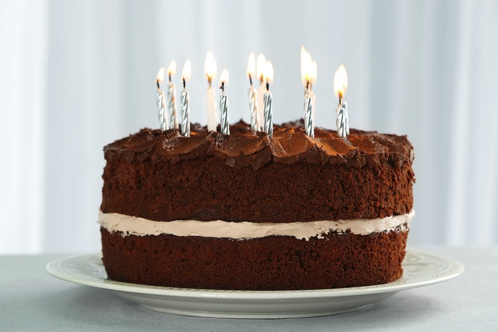 Delicious chocolate cake with candles on table on light background