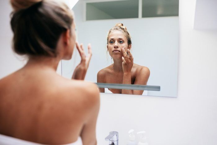 Woman in bathroom looking in to mirror and applying cream on her face . Beautiful female pampering her facial skin.