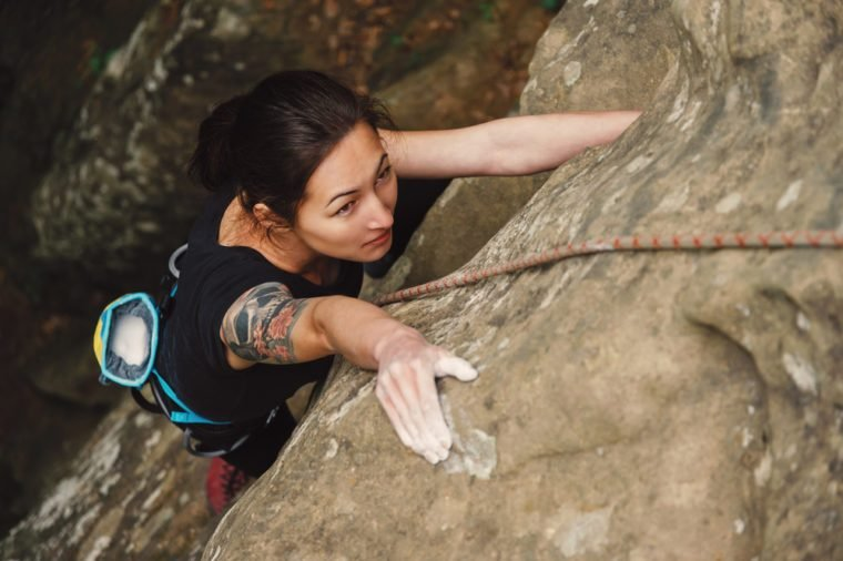 Beautiful young woman climbing on rock outdoor in summer, top view