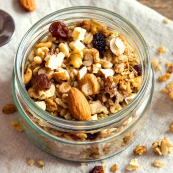 Homemade granola with nuts and seeds in glass jar for healthy breakfast