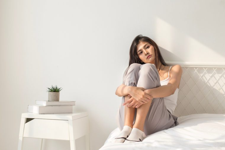 Asian woman with sad emotion in bedroom