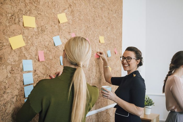Two women are at work in an office. They are standing at a cork board and are having a discussion as they pin things up.