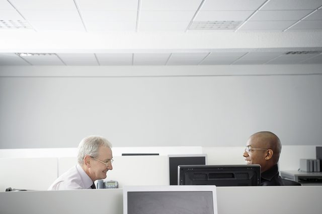 Multiethnic business people having casual meeting in office cubicle