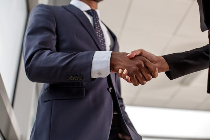 Good work. Low angle close-up of strong handshake of intelligent businesspeople. Elegant man and woman are standing in office wearing formal clothes