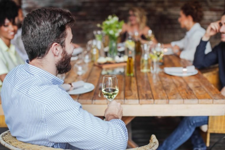 Group of people sitting outdoor and having fun time on dinner party celebration and drinking wine.
