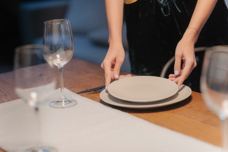 Young woman setting up table for dinner party at home.