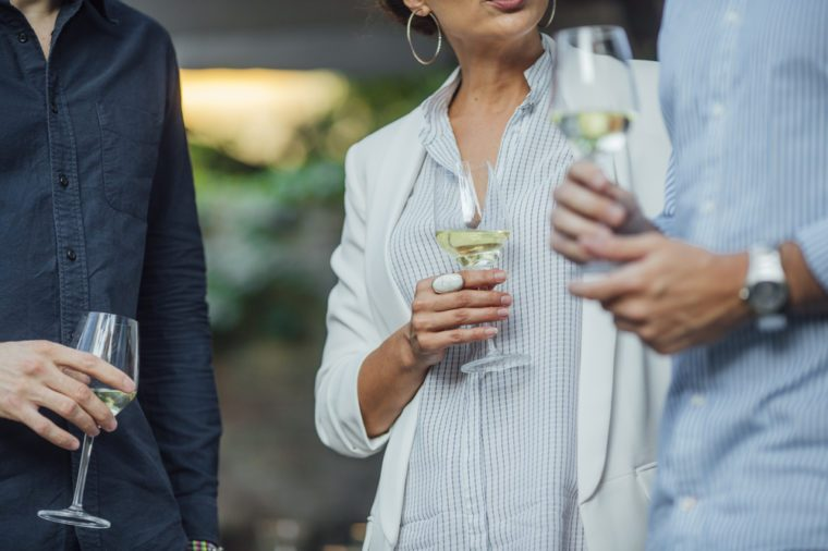 Cropped unrecognisable men and woman holding glasses of white wine and standing outdoor.