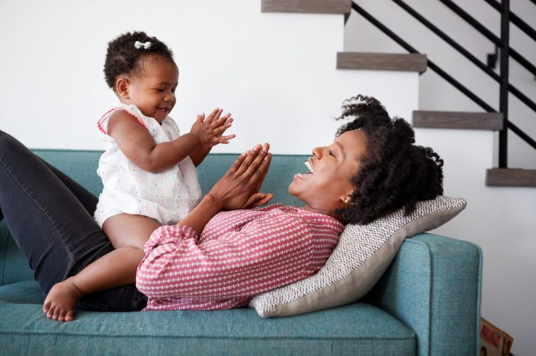 Mother Lying On Sofa At Home Playing Clapping Game With Baby Daughter