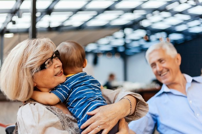 Grandparents With Their Grandson Spending Lovely Time At Cafe