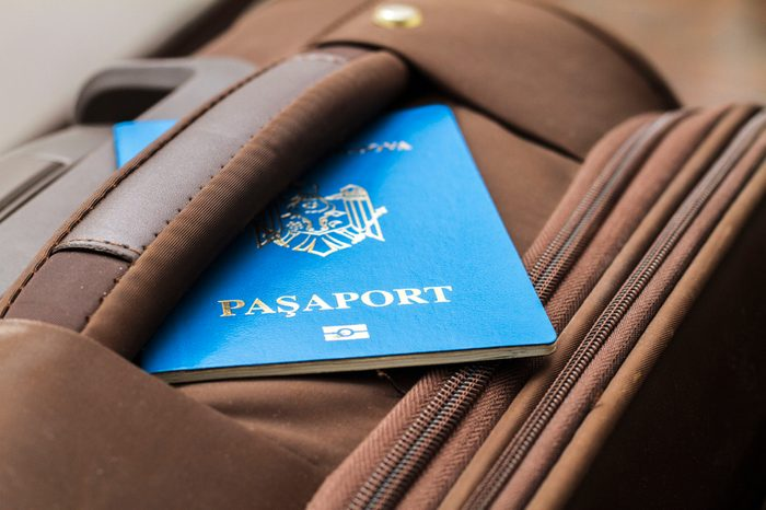 Brown travel suitcase and blue generic passport close up view. Tourism and leisure concept. Selective focus and shallow DOF