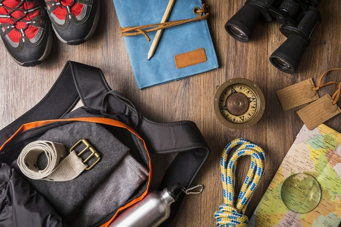 Overhead view of travel equipment for a backpacking trip on wooden floor. / Items include rope, belt, canteen, compass, map, binoculars, journal, boots, note book, backpack. Time to travel concept.