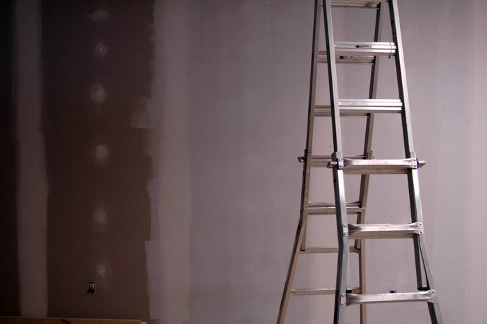 Painting drywall using ladder