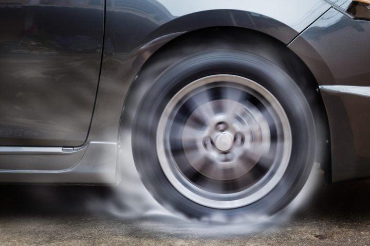Car racing spinning wheel burns rubber on floor.