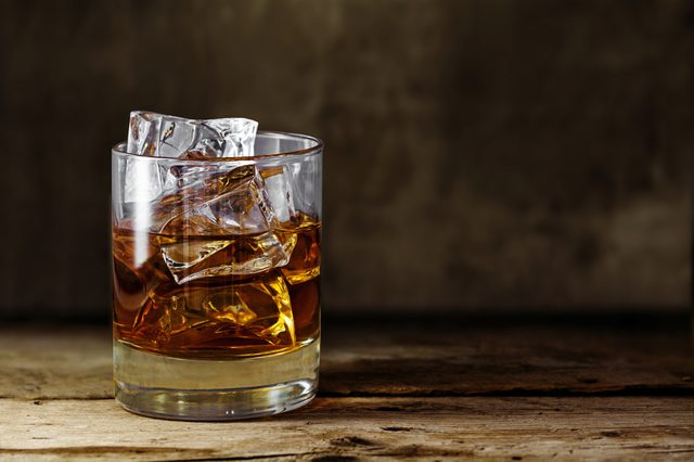 glass of scotch whiskey with ice cubes on a rustic wooden table, copy space in the brown background
