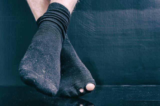 Legs bankrupt in black holey socks on a black background