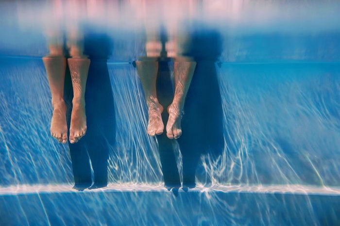 adults legs underwater in the swimming pool