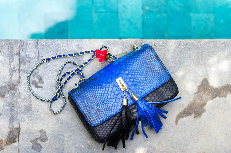 Stylish fashion handmade snakeskin python handbag on a swimming pool background. Bali.