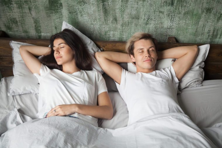 Young couple resting together with eyes closed sleeping well in comfortable bed before waking up in the morning, woman and man lying asleep in cozy bedroom at home, healthy good night sleep concept