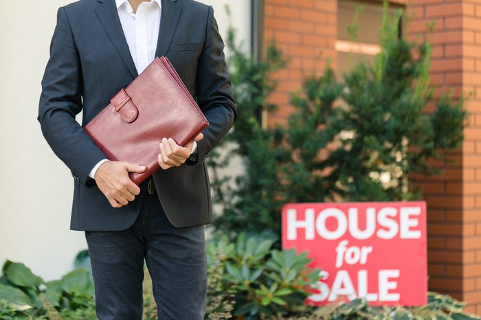 Close-up of businessman in black suit holding brown leather briefcase standing next to a house for sale