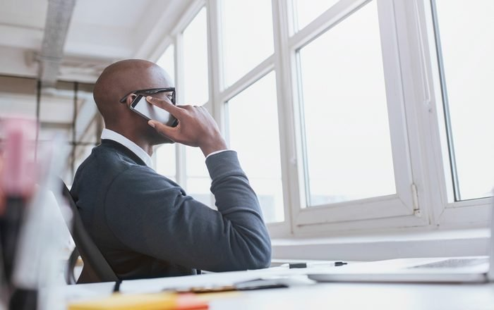 Young african man sitting at his desk talking on his mobile phone in office. African executive using cell phone while at work.