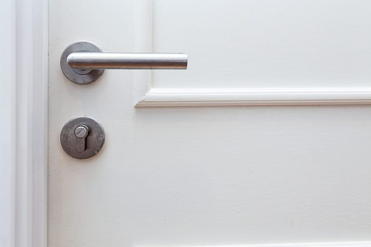 Metallic knob handle with hole key on white door. Closed up with copy space.