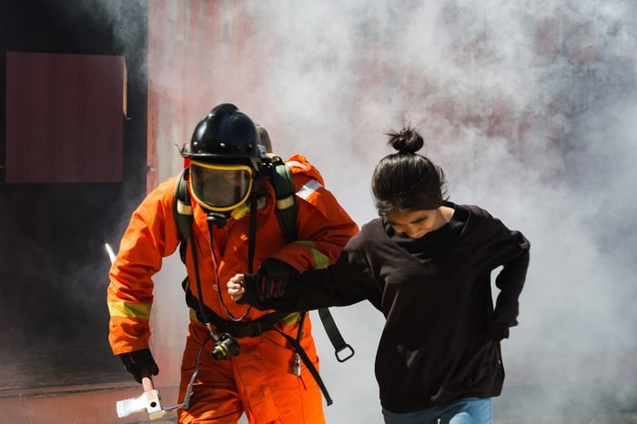 Firefighter help the Asian child in the burning warehouse / Fire and rescue training school regularly to get ready.