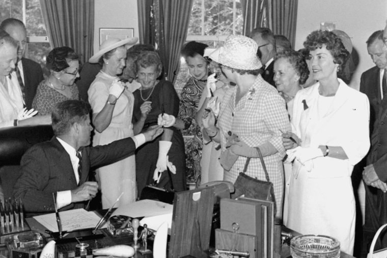 President Kennedy passes out pens, at the White House after signing a bill to provide equal pay for women. From left: Ethlyn Christensen of the YWCA; Rep. Leonor Sullivan, D-MO; Mrs. Joseph Willen of the National Council of Jewish Women; Rep. Edna Kelly, D-NY; Margaret Mealey, foreground, checkered dress, of the National Council of Catholic Women; Rep. Edith Green, D-OR; and Mrs. Carolyn Davis of the United Auto Workers