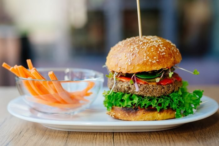 Delicious Mexican vegan burger with chickpeas, onion, lettuce and spicy chili sauce