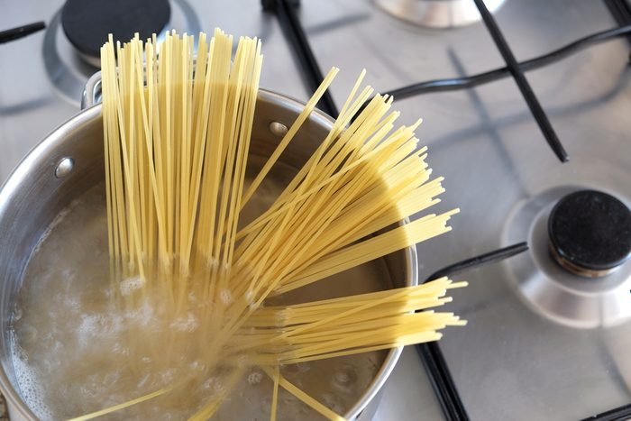 Boiling spaghetti in a silver pot with hot water