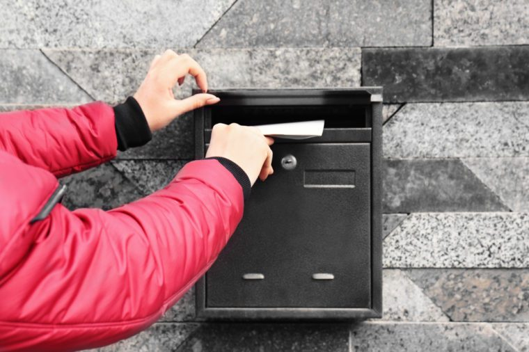 Woman putting envelope into mailbox on wall of building outdoors