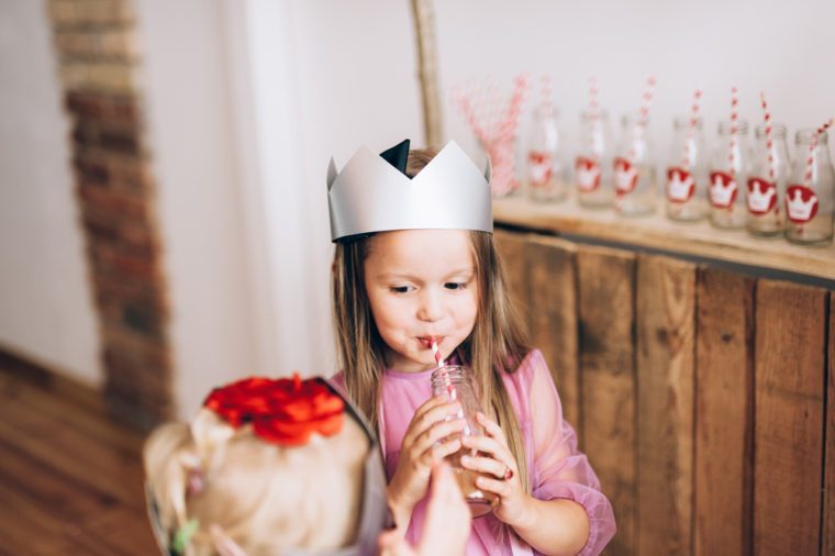 Young little girl wearing princess crown and pink dress, smiling, drinking juice and celebrating her birthday