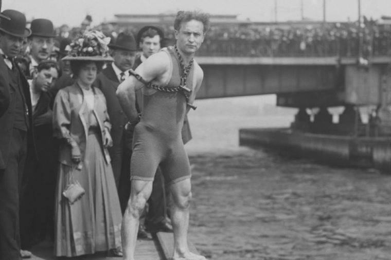 Harry Houdini jumps 30 feet from Harvard Bridge locked up in chains, April 30, 1908. Boston, Massachusetts. His hands were handcuffed and chained to a collar around his neck by a Boston policeman in f