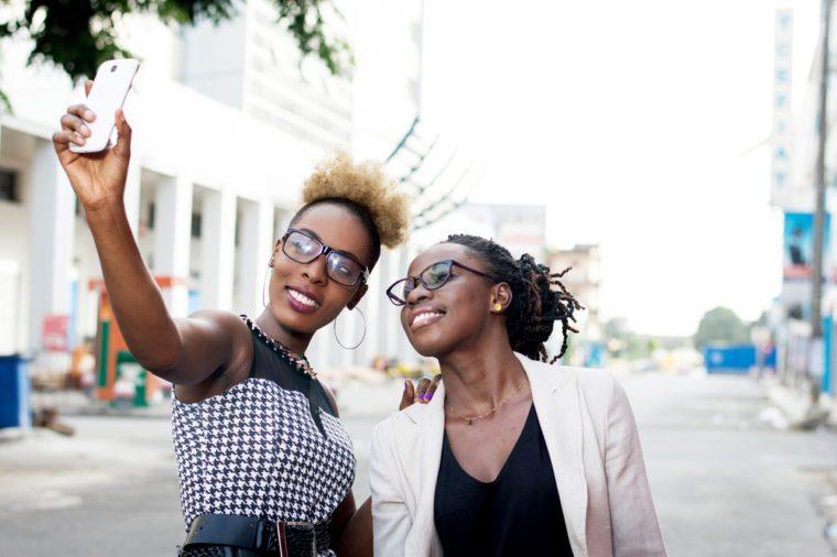 Two happy businesswomen taking selfie by smart phone outside