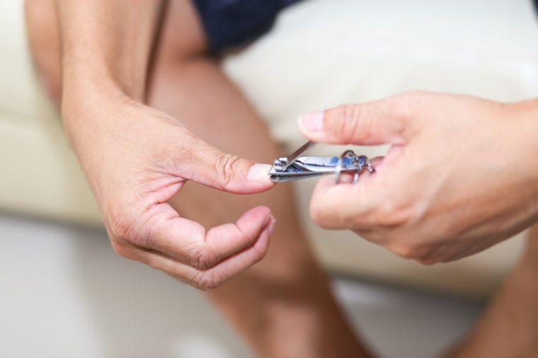 Man cutting his nails using nail clipper