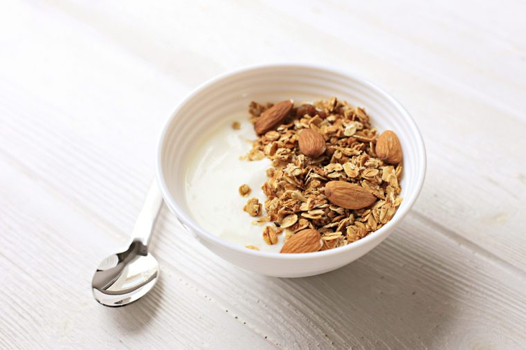 Bowl of whole grain muesli with yogurt on white wooden background, top view