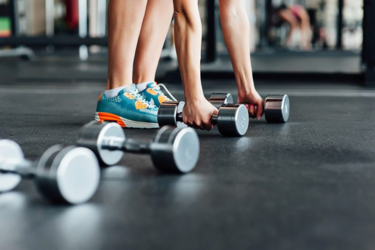 Body and mind workout in fitness studio. Closeup on woman lifting dumbbell from the floor