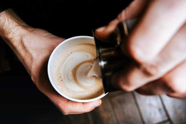 Barista making coffee latte art. Process of making latte art.