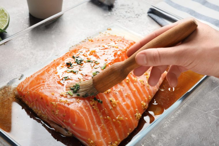 Woman marinating raw salmon in dish at table