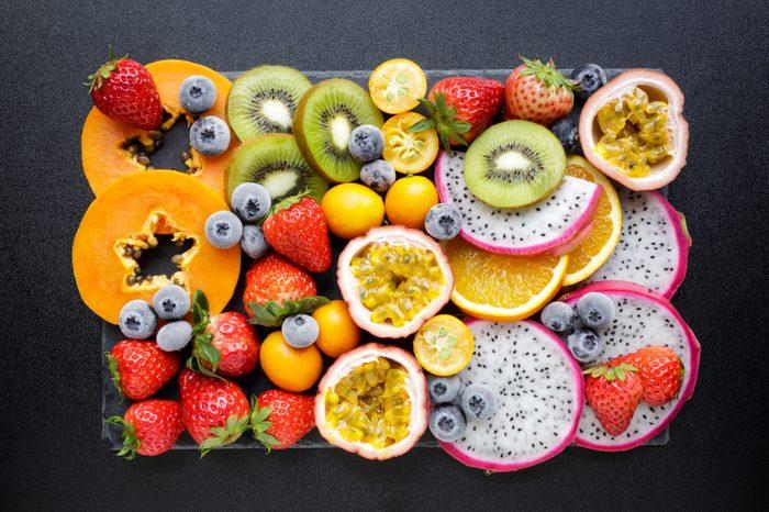 Fresh fruits on a black background. Exotic fresh fruits on a blackboard.Strawberry, blueberry, papaya, dragon fruit, kiwi, passion fruit.