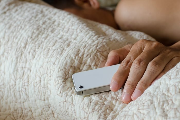 Man sleeping in bed and holding a mobile phone. Concept photo of smart phone addiction
