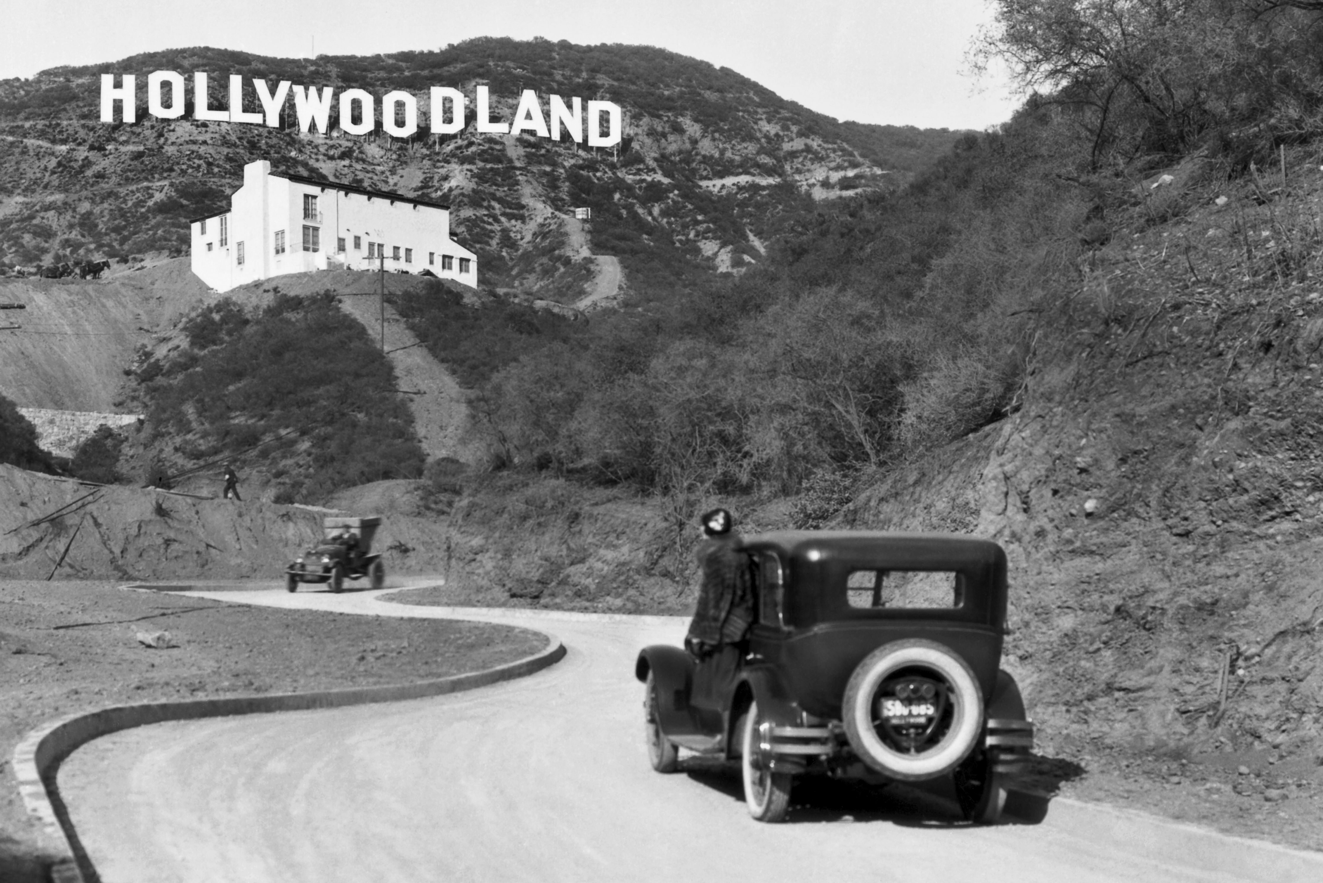 Mandatory Credit: Photo by Underwood Archives/UIG/Shutterstock (3838241a) Hollywood, Los Angeles:  c. 1924 A sign advertises the opening of the Hollywoodland housing development in the hills on Mulholland Drive overlooking Los Angeles. The white building below the sign is the Kanst Art Gallery, which opened on April 1, 1924 VARIOUS