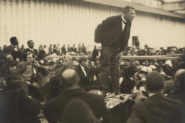 Booker T. Washington (1856-1915), speaking on a raised platform in Mound Bayou, Mississippi. 1912 photo by Arthur P. Bedou.