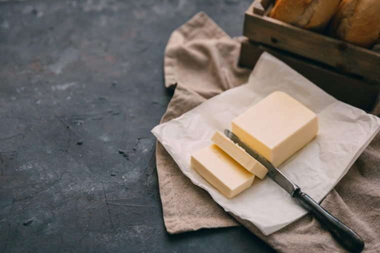 Pat of fresh farm butter with a knife and bread over rustic background