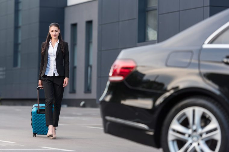 Young beautiful woman in pant suit walking towards passenger car with suitcase