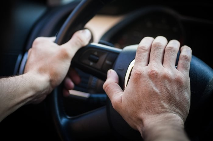 Color image of a hand honking the horn inside a car.