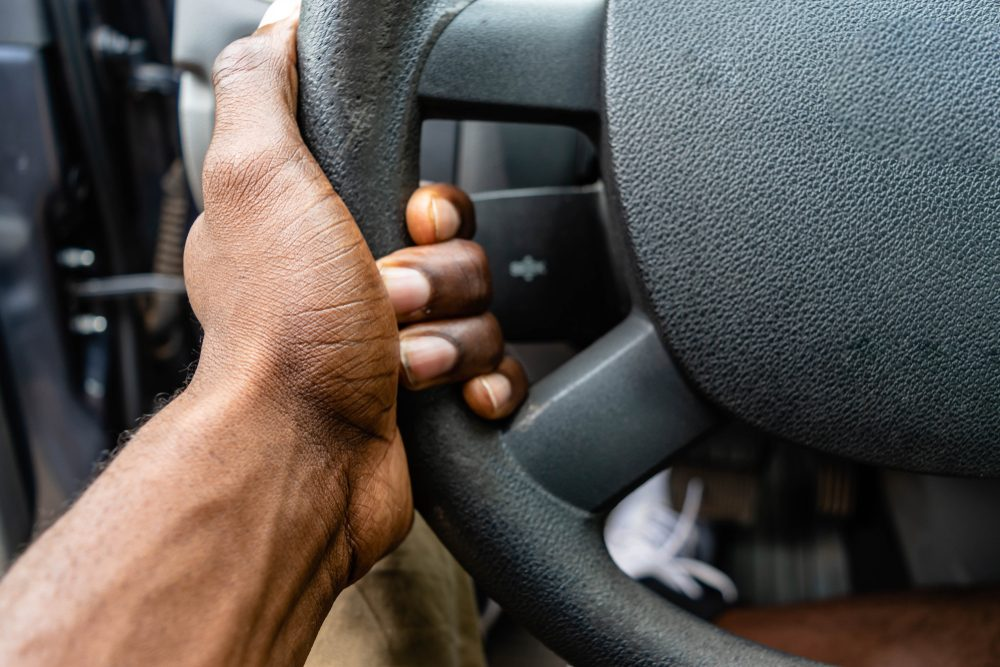 Close-up Of A Black African American Man Hands Holding Steering Wheel While Driving Car. Detail of a hand holding a steering wheel.