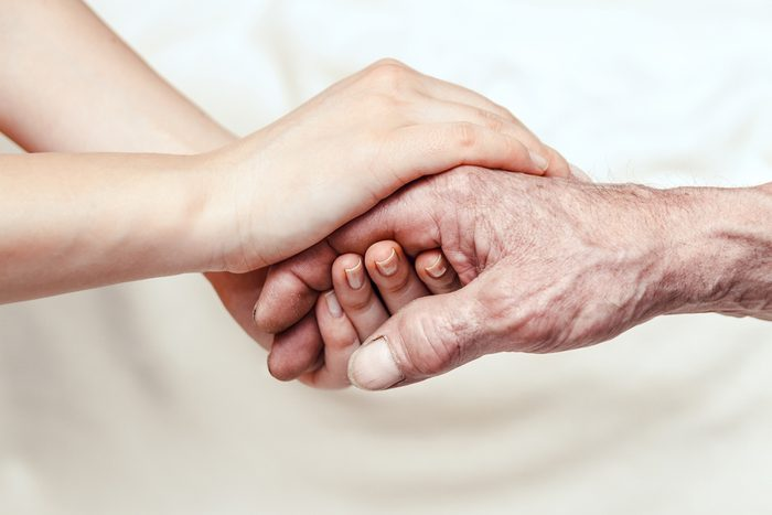 Hands of the old man and a young woman. close up. toning