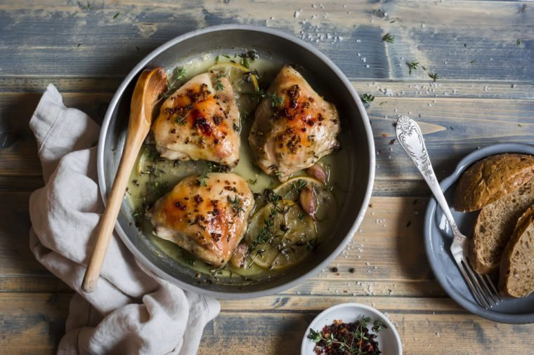 Baked chicken in white wine in the pan. On rustic wooden background, top view